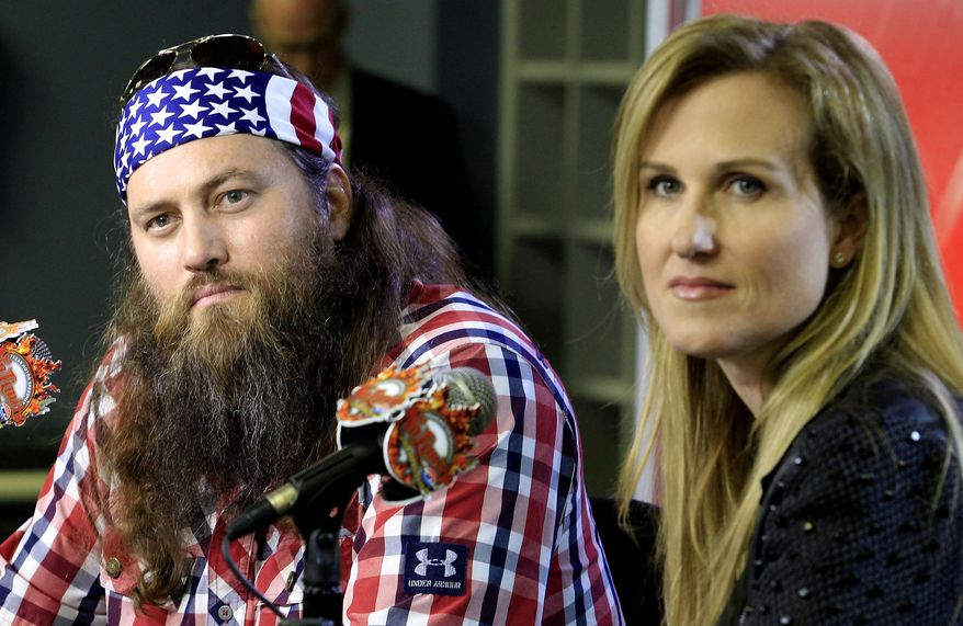 """Duck Dynasty stars Willie and Korie Robertson at Texas Motor Speedway debuted their new Big Hoss TV, a 218 x 94 foot screen over the east grandstands of the racetrack, Wednesday, March 19, 2014. The first show to be seen on the screen by the public is Wednesday's episode of """"Duck Dynasty"""", sponsors of the upcoming April NASCAR race, the Duck Commander 500. (AP Photo/The Fort Worth Star-Telegram, Paul Moseley)"""
