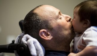 In this photo taken March 14, 2014, Captain Bill Dowling gives a kiss to his friend's three-month-old son Ryan Rainville in Tomball, Texas. Dowling receives friends and colleagues to this home in Tomball everyday.  Dowling suffered serious brain injuries and lost both his legs after fighting a massive motel fire on May 31, 2013. He was this year's grand marshal for the 55th annual St. Patrick's parade saluting Houston's first responders. (AP Photo/Houston Chronicle, Marie D. De Jesus)