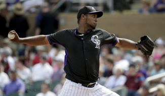 Colorado Rockies starting pitcher Juan Nicasio throws to the Milwaukee Brewers during the first inning of a spring exhibition baseball game in Scottsdale, Ariz., Thursday, March 20, 2014. (AP Photo/Chris Carlson)