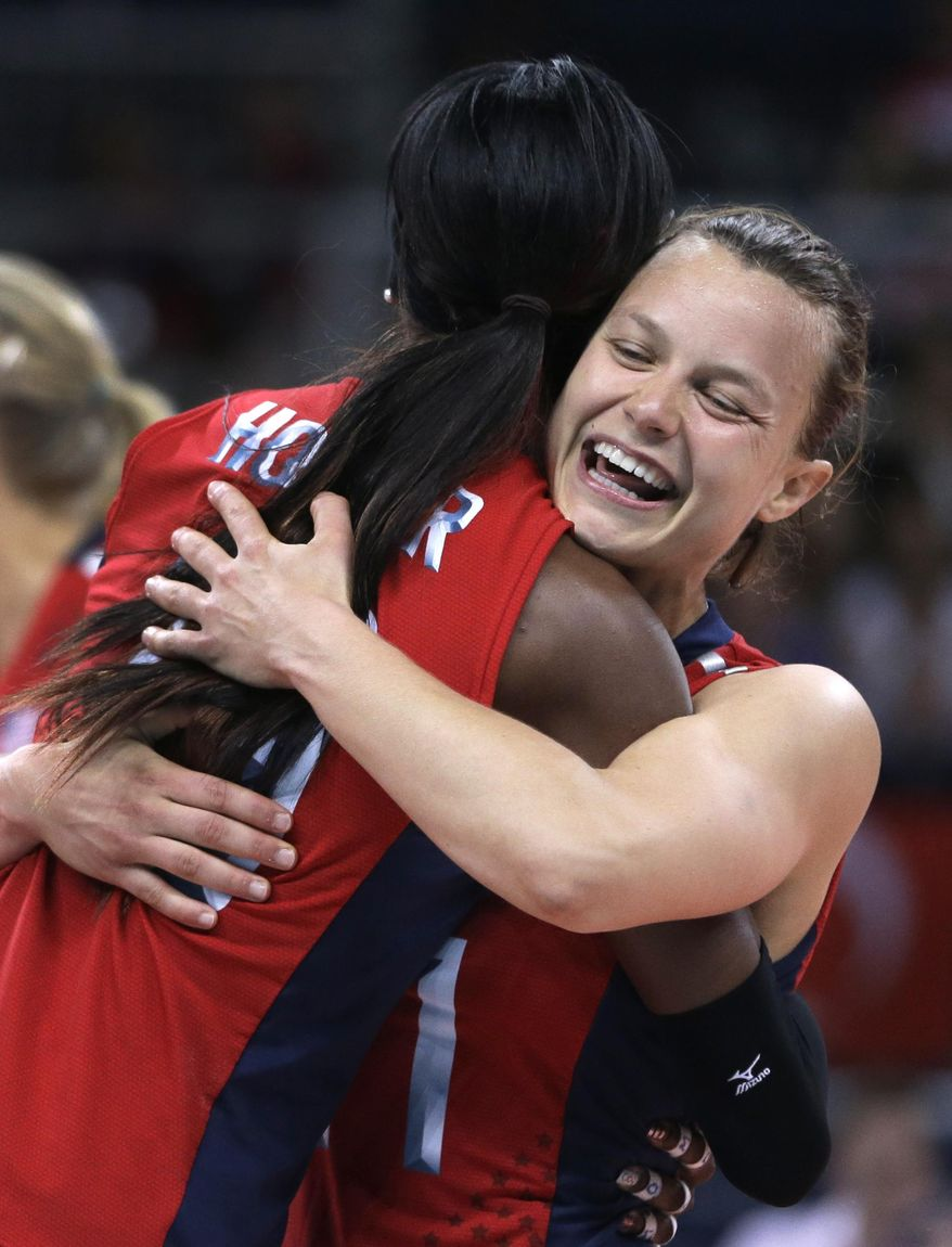 ADVANCE FOR WEEKEND EDITIONS, MARCH 22-23 - FILE - In this Aug. 5, 2012, file photo, United States' Destinee Hooker, left, gets a hug from teammate Courtney Thompson during a women's preliminary volleyball match against Turkey at the 2012 Summer Olympics in London. With the Rio Olympics still over two years away, many players on the U.S. volleyball team are working their day jobs: Playing for professional volleyball teams overseas. (AP Photo/Jeff Roberson, File)