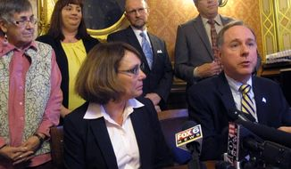Republican Majority Leader Pat Strachota, seated left, listens as Speaker Robin Vos, right, explains changes to a bill making oral chemotherapy more affordable on Thursday, March 20, 2014, in Madison, Wis. Standing behind the speakers are cancer support advocates from left to right: Janice Krukowski, Jennifer Grandkowski, and Paul Westrick and Rep. John Nygren. (AP Photo/Scott Bauer)