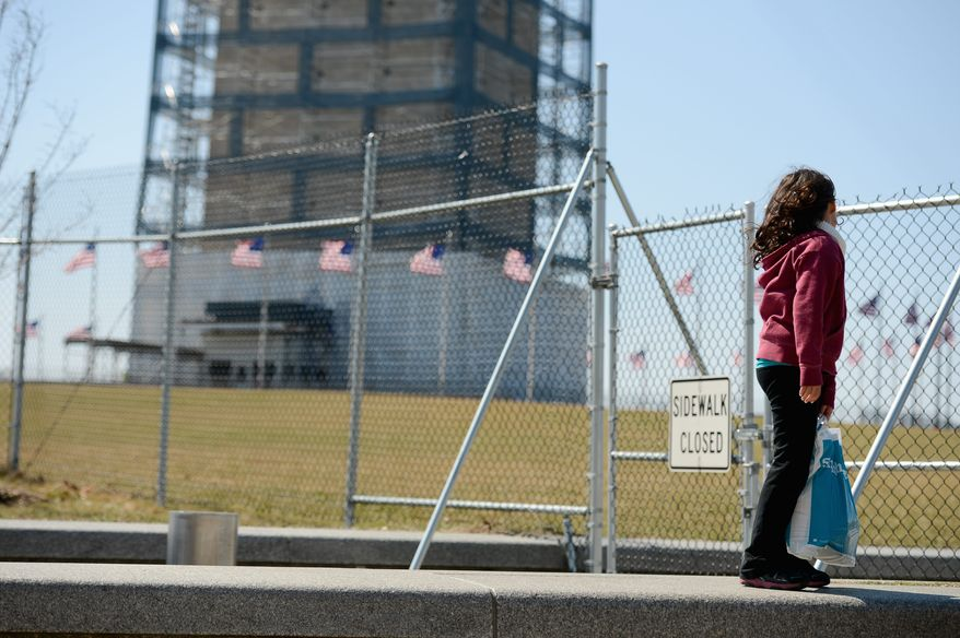 Emily Boyd, 8, of Columbia, S.C. walks along the fence near the Washington Monument which is set to reopen in May, Washington, D.C., Thursday, March 20, 2014. The monument has been closed since 2011 for earthquake damage repairs.) (andrew harnik/the washington times)