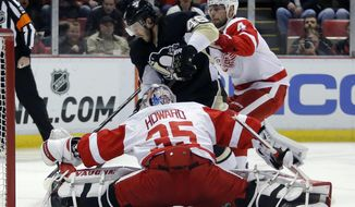 Detroit Red Wings goalie Jimmy Howard (35) stops a shot by Pittsburgh Penguins' Deryk Engelland (46) as Red Wings' Jakub Kindl (4) helps defend the goal during the first period of an NHL hockey game Thursday, March 20, 2014 in Detroit. (AP Photo/Duane Burleson)