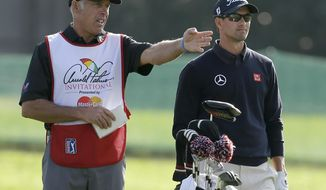 Caddie Steve Williams, left, gestures as he talks to Adam Scott, of Australia, on the 16th fairway during the first round of the Arnold Palmer Invitational golf tournament at Bay Hill Thursday, March 20, 2014, in Orlando, Fla. (AP Photo/Chris O'Meara)