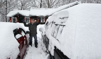 Donald Croteau works to clear nearly a foot of snow off his car on the first day of spring, Thursday, March 20, 2014 in North Woodstock, N.H.  Much of the country remains in a deep freeze, delaying the risk of spring flooding into April in the upper Midwest to New England. While major flooding is not expected, experts say there's a moderate risk of flooding in the southern Great Lakes region because of above-average snowpack. (AP Photo/Jim Cole)