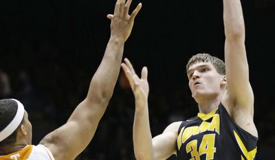 Iowa center Adam Woodbury (34) shoots over Tennessee forward Jarnell Stokes (5) in the second half of a first-round game of the NCAA college basketball tournament on Wednesday, March 19, 2014, in Dayton, Ohio. (AP Photo/Al Behrman)