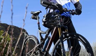 In this photo taken March 7, 2014, Brian Grossman, poses with his mountain bike near Shevlin Park in Bend, Ore.  Grossman is racing the Cape Epic, an eight-day, 445-mile mountain bike race in South Africa that includes more than 48,720 feet of vertical climbing in temperatures over 100 degrees. Grossman is racing to raise funds and awareness for Kids in the Game, a Bend nonprofit he co-founded that provides financial support for underprivileged youths to help them get active and participate in sports. (AP Photo/The Bulletin, Robb Kerr)