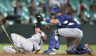 Team Australia's Mike Walker, left, is tagged out at home by Los Angeles Dodgers catcher A.J. Ellis during their exhibition baseball game at the Sydney Cricket Ground in Sydney, Thursday, March 20, 2014. The Arizona Diamondbacks and the Dodgers open the Major League Baseball regular season with games on Saturday and Sunday. (AP Photo/Rick Rycroft)