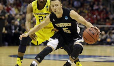 Wofford guard Eric Garcia (5) drives the ball against Michigan guard Zak Irvin (21) during the first half of a second round NCAA college basketball tournament game Thursday, March 20, 2014, in Milwaukee. (AP Photo/Jeffrey Phelps)