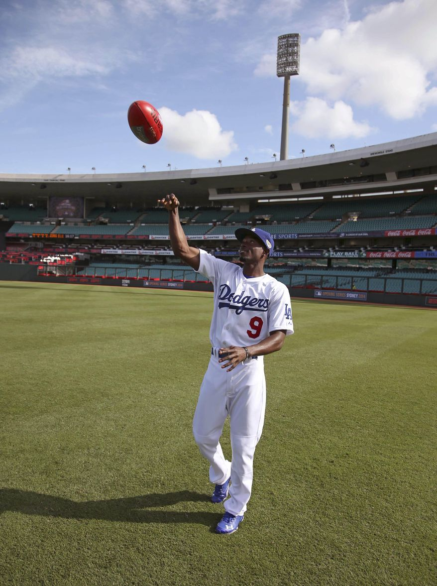 The Los Angeles Dodgers' Dee Gordon throws an Australian rules football during a training at the Sydney Cricket Ground in Sydney, Wednesday, March 19, 2014. The MLB season-opening two-game series between the Los Angeles Dodgers and Arizona Diamondbacks in Sydney will be played this weekend. (AP Photo/Rick Rycroft)