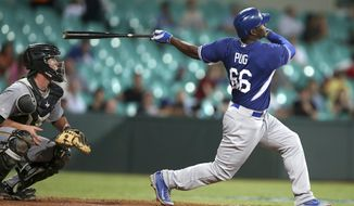 Los Angeles Dodgers' Yasiel Puig hits a two-run home run during their exhibition baseball game against Team Australia at the Sydney Cricket Gground in Sydney, Thursday, March 20, 2014. The Arizona Diamondbacks and the Dodgers open the Major League Baseball regular season with games on Saturday and Sunday. (AP Photo/Rick Rycroft)