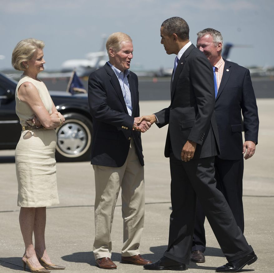 President Barack Obama is greeted by Sen. Bill Nelson, D-Fl., center, his wife Grace Nelson, left, and Orlando, Fla. Mayor John Dyer, right, upon his arrival at Orlando International Airport in Orlando, Fla., Thursday, March 20, 2014. Obama is visiting Valencia College to highlight women's economic issues. He will also then travel to Miami for a pair of fundraisers for the democrats before returning to Washington later tonight. (AP Photo/Pablo Martinez Monsivais)