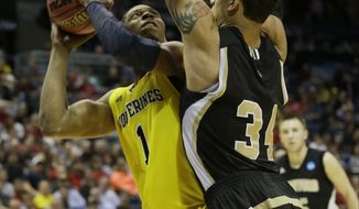 Michigan forward Glenn Robinson III (1) drives to the basket against Wofford forward Lee Skinner (34) during the first half of a second round NCAA college basketball tournament game Thursday, March 20, 2014, in Milwaukee. (AP Photo/Morry Gash)