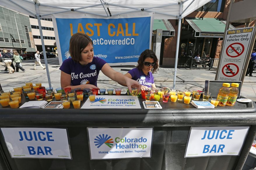 Lauren Farnsworth, left, and April Buell hand out literature and juice shots from a mock bar on an outdoor pedestrian mall, encouraging the public to get health coverage under the Affordable Care Act, during a promotional campaign launched by Colorado HealthOP, an independent non-profit health care co-op, in Denver, Thursday March 20, 2014. More than 250,000 Coloradans have become covered through the state-run insurance exchange since enrollment began October 1, 2013, and those who still do not have health insurance have two more weeks to get coverage or pay a fine. (AP Photo/Brennan Linsley)