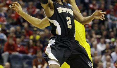 Wofford guard Karl Cochran (2) goes to the basket against Michigan forward Jon Horford during the first half of a second round NCAA college basketball tournament game Thursday, March 20, 2014, in Milwaukee. (AP Photo/Jeffrey Phelps)