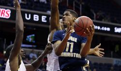 George Washington guard Kethan Savage (11) drives to the basket as he is covered by Maryland forward Jonathan Graham, left, and Dez Wells, during the second half of an NCAA college basketball game in the BB&T Classic, Sunday, Dec. 8, 2013, in Washington. (AP Photo/Alex Brandon)