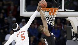 Cincinnati's Justin Jackson (5) tries to stop a shot by Harvard's Steve Moundou-Missi in the first half during a second-round game of the NCAA college basketball tournament in Spokane, Wash., Thursday, March 20, 2014. (AP Photo/Elaine Thompson)