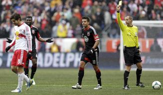 FILE - In this March 16, 2013, file photo, referee Mark Geiger, right, issues a yellow card to New York Red Bulls midfielder Juninho, left, as D.C. United midfielder Brandon McDonald, center left, and Marcelo Saragosa look on during the second half of an MLS soccer game in Harrison, N.J.  The lockout of Major League Soccer's referees has ended following an agreement on a five-year labor contract. The Professional Referee Organization, which manages game officials for the U.S. Soccer Federation and MLS, and the Professional Soccer Referee Association announced the agreement on Thursday, March 19, 2014. (AP Photo/Julio Cortez, File0