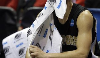 Wofford guard Eric Garcia watches from the bench during the second half of a second round NCAA college basketball tournament game Thursday, March 20, 2014, in Milwaukee. Michigan won 57-40. (AP Photo/Morry Gash)