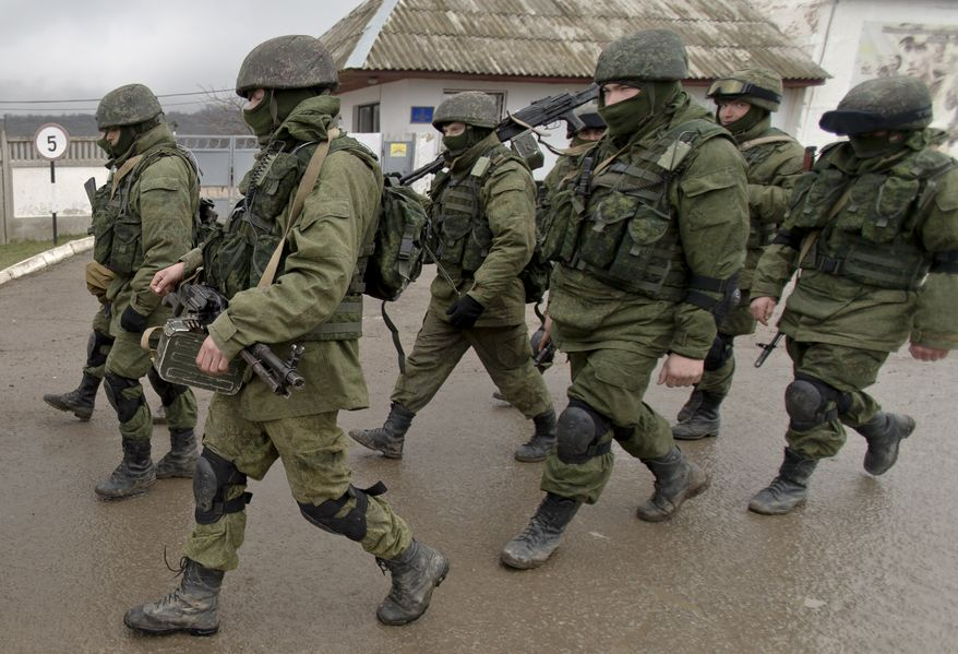 Pro-Russian soldiers march outside an Ukrainian military base in Perevalne, Crimea, Thursday, March 20, 2014. With thousands of Ukrainian soldiers and sailors trapped on military bases, surrounded by heavily armed Russian forces and pro-Russia militia, the Kiev government said it was drawing up plans to evacuate its outnumbered troops from Crimea back to the mainland and would seek U.N. support to turn the peninsula into a demilitarized zone.(AP Photo/Vadim Ghirda)