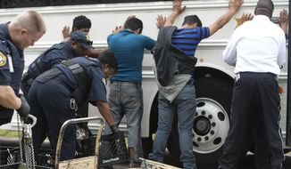 Authorities search people, Wednesday, March 19, 2014, in southeast Houston. A house overflowing with more than 100 people presumed to be in the U.S. illegally was uncovered just outside Houston on Wednesday, a police spokesman said. The suspected stash house was found during a search for a 24-year-old woman and her two children that were reported missing by relatives Tuesday after a man failed to meet them, said a spokesman for the Houston Police Department. (AP Photo/Houston Chronicle, Cody Duty)