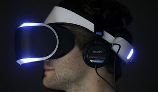 Marcus Ingvarsson tests out the PlayStation 4 virtual reality headset Project Morpheus in a demo area at the Game Developers Conference 2014 in San Francisco, Wednesday, March 19, 2014.  (AP Photo/Jeff Chiu)