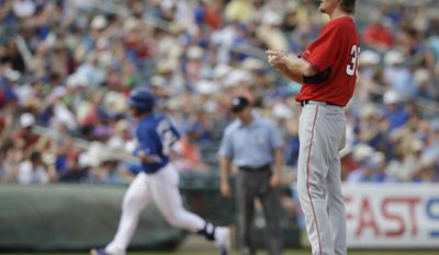 Los Angeles Angels starting pitcher Jered Weaver rubs up a new baseball after giving up a home run to Kansas City Royals' Jason Donald during the sixth inning of a spring exhibition baseball game Thursday, March 20, 2014, in Surprise, Ariz. (AP Photo/Darron Cummings)