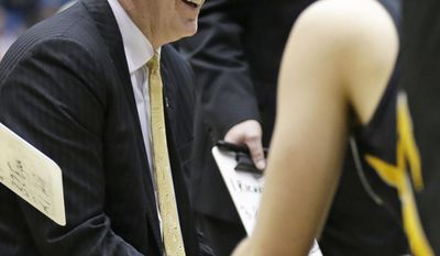 Iowa head coach Fran McCaffery smiles as he talks with his players during a timeout in the second half of a first-round game against Tennessee in the NCAA college basketball tournament on Wednesday, March 19, 2014, in Dayton, Ohio. (AP Photo/Al Behrman)