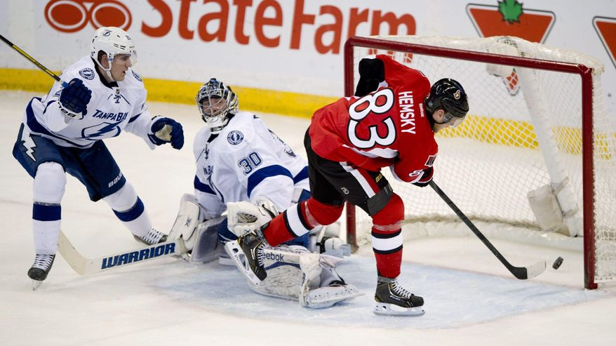 Tampa Bay Lightning defenseman Matt Carle, left, and goalie Ben Bishop watch as Ottawa Senators right wing Ales Hemsky fires the puck into the net during the second period of an NHL hockey game Thursday, March 20, 2014, in Ottawa, Ontario. (AP Photo/The Canadian Press, Adrian Wyld)
