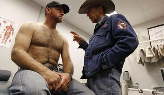 In this photo from Nov. 9, 2013, Dr. Tandy Freeman, right, an orthopedic surgeon, talks to rodeo rider Scooter Nolen after Nolen's horse fell and injured Nolen's shoulder recently in Allen, Texas. Dr. Freeman attended to cowboys competing in the Tom Thumb Texas Stampede rodeo. (AP Photo/The Dallas Morning News, Nathan Hunsinger) MANDATORY CREDIT; MAGS OUT; TV OUT; INTERNET USE BY AP MEMBERS ONLY; NO SALES