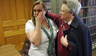 Kelli Jo Griffin, left, Montrose, Iowa, wipes away tears as she is embraced by Sister Peggy from the Holy Family Catholic Church of Fort Madison, following her not guilty verdict Thursday March 20, 2014 in Keokuk, Iowa. The former drug offender, who believed her voting rights had been restored when she cast a ballot last year, was acquitted of perjury - a public rebuke of Iowa's two-year investigation into voter fraud. It was the first trial stemming from the state's voter fraud investigation championed by Secretary of State Matt Schultz, a Republican. (AP Photo/The Hawk Eye, John Gaines)
