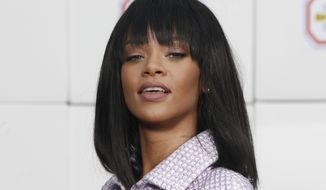 FILE - In this Tuesday, March 4, 2014 file photo, singer Rihanna poses as she arrives to Chanel's ready to wear fall/winter 2014-2015 fashion collection presented in Paris. A judge on Thursday, March 20, 2014, upheld the firing of former Los Angeles police officer Rebecca Reyes for distributing an evidentiary photo of Rihanna's injuries after Chris Brown attacked her in February 2009. The photo was leaked to TMZ, although Reyes denies she sent the photo to the celebrity website.  (AP Photo/Thibault Camus, file)
