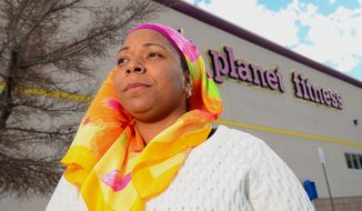 Tarainia McDaniel is photographed in front of Planet Fitness in Albuquerque, N.M., March 2, 2014.  The Albuquerque Planet Fitness refused to let McDaniel a New Mexico Muslim woman,  wear her religious head covering when she tried to work out, according to a new lawsuit. An attorney for McDaniel, 37, recently filed the lawsuit in a New Mexico district court stemming after a 2011 clash that prevented McDaniel from using the gym, even though court documents said another Planet Fitness had previously let her.  (AP Photo/The Albuquerque Journal, Adolphe Pierre-Louis)