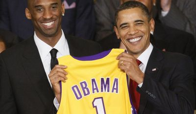 **FILE** President Barack Obama holds a personalized Los Angeles Lakers team jersey presented to him by Lakers guard Kobe Bryant (left) as he honored the 2009 NBA champions Lakers in the East Room of the White House on Jan. 25, 2010. (Associated Press)