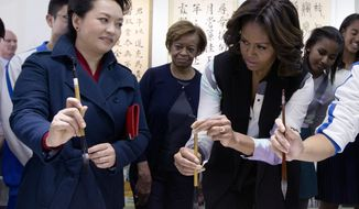 Peng Liyuan, wife of Chinese President Xi Jinping, left, shows U.S. first lady Michelle Obama, center, how to hold a writing brush as they visit a Chinese traditional calligraphy class at the Beijing Normal School, a school that prepares students to go abroad in Beijing, China Friday, March 21, 2014. (AP Photo/Andy Wong, Pool)