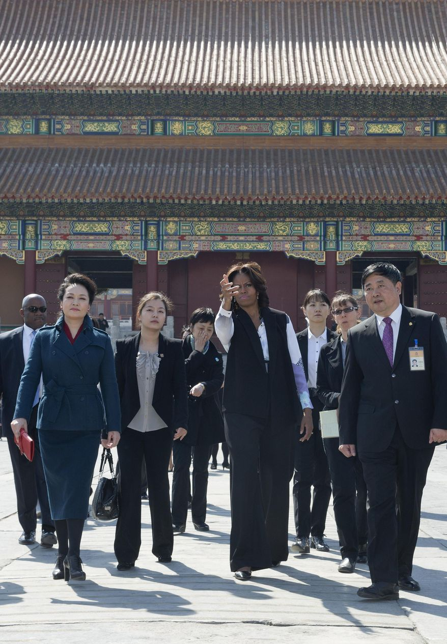 U.S. first lady Michelle Obama, center, and Peng Liyuan, wife of Chinese President Xi Jinping, left,  walk together at Forbidden City in Beijing, China Friday, March 21, 2014. (AP Photo/Andy Wong, Pool)