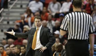 Oklahoma State coach Travis Ford talks to a referee during the second half in a second-round game against Gonzaga in the NCAA men's college basketball tournament Friday, March 21, 2014, in San Diego. (AP Photo/Gregory Bull)