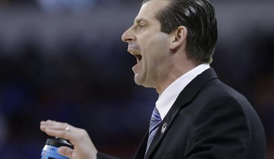 Massachusetts head coach Derek Kellogg speaks to players during the first half of an NCAA college basketball second-round tournament game against Tennessee, Friday, March 21, 2014, in Raleigh, N.C. (AP Photo/Gerry Broome)