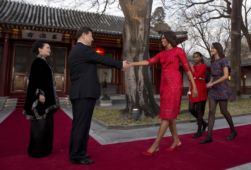 U.S. first lady Michelle Obama, third from right, her daughters Malia, right, and Sasha, second from right, is greeted by Chinese President Xi Jinping, second from left, and his wife Peng Liyuan, left, at the Diaoyutai State guest house in Beijing, China Friday, March 21, 2014. U.S. first lady Michelle Obama met with excited students who were building robots and tried her hand at Chinese calligraphy Friday during a tour of a Beijing high school. (AP Photo/Andy Wong, Pool)