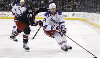Columbus Blue Jackets' Ryan Johansen (19) checks New York Rangers' Rick Nash (61) during the first period of an NHL hockey game, Friday, March 21, 2014, in Columbus, Ohio. (AP Photo/Mike Munden)