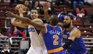 Philadelphia 76ers' Michael Carter-Williams, left, tries to keep the ball away from New York Knicks' Raymond Felton, center, and Tyson Chandler during the first half of an NBA basketball game, Friday, March 21, 2014, in Philadelphia. (AP Photo/Matt Slocum)