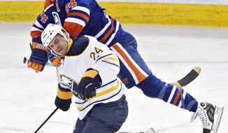 Buffalo Sabres' Zenon Konopka (24) is hit by Edmonton Oilers' Ryan Smyth (94) during the second period of an NHL hockey game in Edmonton, Alberta, on Thursday, March 20, 2014. (AP Photo/The Canadian Press, Jason Franson)