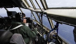 Japanese Air Self-Defense Force copilot Ryutaro Hamahira scans the ocean aboard a C130 aircraft while it flies over the southern search area in the southeastern Indian Ocean, 200 to 300 kilometers (124 to 186 miles) south of Sumatra, Indonesia, Friday, March 21, 2014. Search planes scoured a remote patch of the Indian Ocean but came back empty-handed Friday after looking for any sign of the missing Malaysia Airlines jet, another disappointing day in one of the world's biggest aviation mysteries. (AP Photo/Koji Ueda)