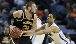 Milwaukee's Matt Tiby (31) protects the ball from Villanova's Josh Hart during the second half of a second-round game in the NCAA college basketball tournament in Buffalo, N.Y., Thursday, March 20, 2014. (AP Photo/Frank Franklin II)