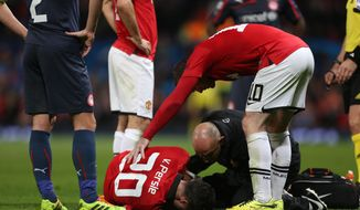 Manchester United's Robin van Persie, bottom, lies injured after colliding with Olympiakos's Kostas Manolas during their  Champions League last 16 second leg soccer match at Old Trafford Stadium, Manchester, England, Wednesday, March 19, 2014. (AP Photo/Jon Super)