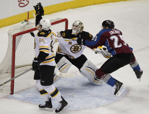 Boston Bruins defenseman Kevan Miller (86) catches the puck as Colorado Avalanche center Maxime Talbot (25) hops toward it against Boston Bruins goalie Chad Johnson (30) the first period of an NHL hockey game in Denver on Friday, March 21, 2014.(AP Photo/Joe Mahone