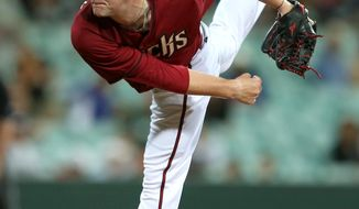 The Arizona Diamondbacks' Archie Bradley follows through while pitching during their exhibition baseball game against Team Australia at the Sydney Cricket ground in Sydney, Friday, March 21, 2014. Major League Baseball will open their season Saturday in Sydney with the Los Angeles Dodgers taking on the Diamondbacks. (AP Photo/Rick Rycroft)