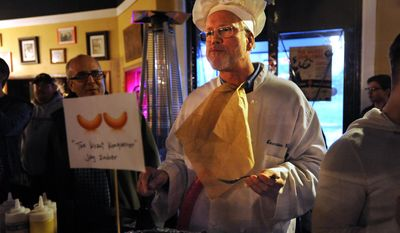 Ypsilanti Mayor Paul Schreiber takes a bite of his 20-foot bratwurst while competing in an eating competition fundraiser for the FLY Children's Art Center at Wurst Bar in Ypsilanti, Mich. Thursday, March 20, 2014. (AP Photo/The Ann Arbor News, Brianne Bowen)