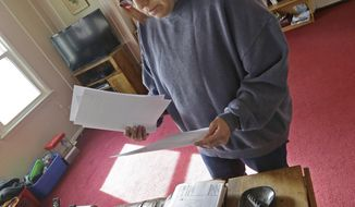 ADVANCE FOR USE MONDAY, MARCH 24, 2014 AT 3 A.M. AND THEREAFTER - Regina Bachman looks through papers dealing flood insurance on her property inside her home in Loveland, Ohio on Friday, March 21, 2014. Bachman bought the home in September 2013 and was initially told by the bank that flood insurance on the property would be affordable, only to find out after closing that the rates were going to increase over $7,000 more annually with new premiums for the National Flood Insurance Program. (AP Photo/Al Behrman)