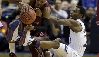 Eastern Kentucky's Corey Walden, left, and Kansas' Andrew Wiggins get tangled up while chasing after a loose ball during the first half of a second-round game in the NCAA college basketball tournament Friday, March 21, 2014, in St. Louis. (AP Photo/Jeff Roberson)